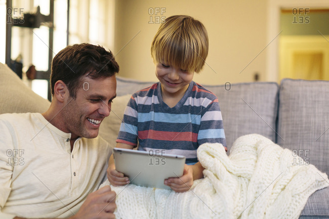 Father with son using tablet computer while sitting at home