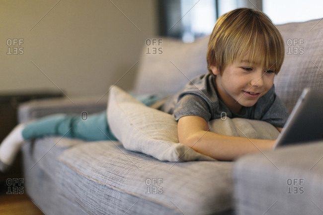 Smiling boy using tablet computer while lying on sofa at home