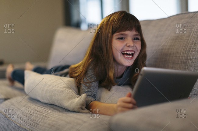 Cheerful girl using tablet computer while lying on sofa at home