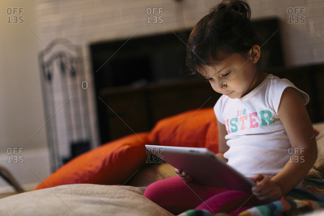 Girl using tablet computer while kneeling at home