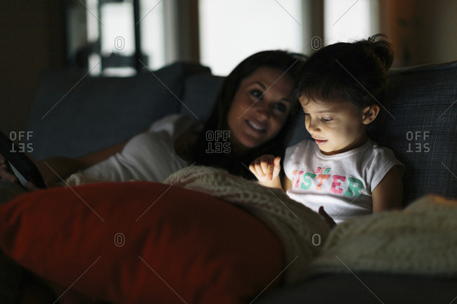 Woman looking at daughter using tablet computer at home