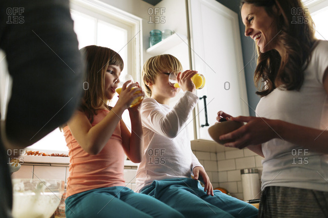 Mother looking at children drinking juice while sitting on kitchen counter