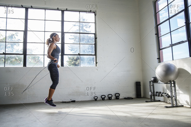 Side view of female athlete skipping with jumping rope in gym