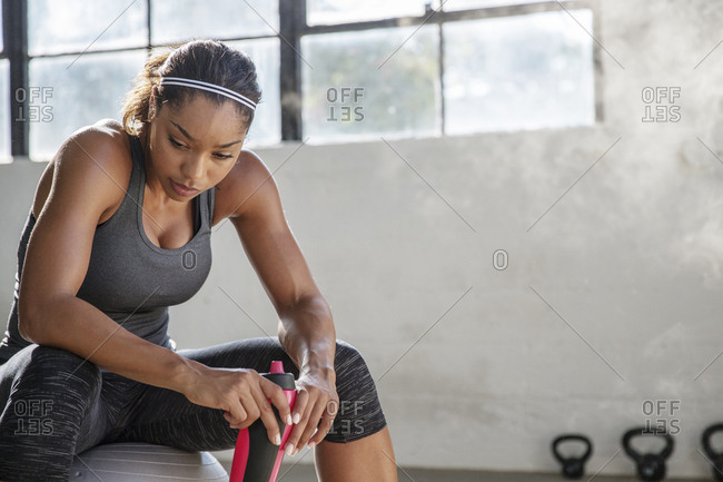 Female athlete holding water bottle relaxing on fitness ball in gym