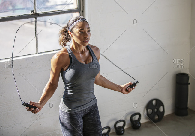High angle view of female athlete skipping with jumping rope in gym