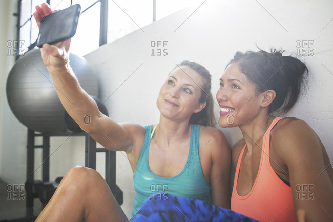 Happy female friends taking selfie through mobile phone in health club