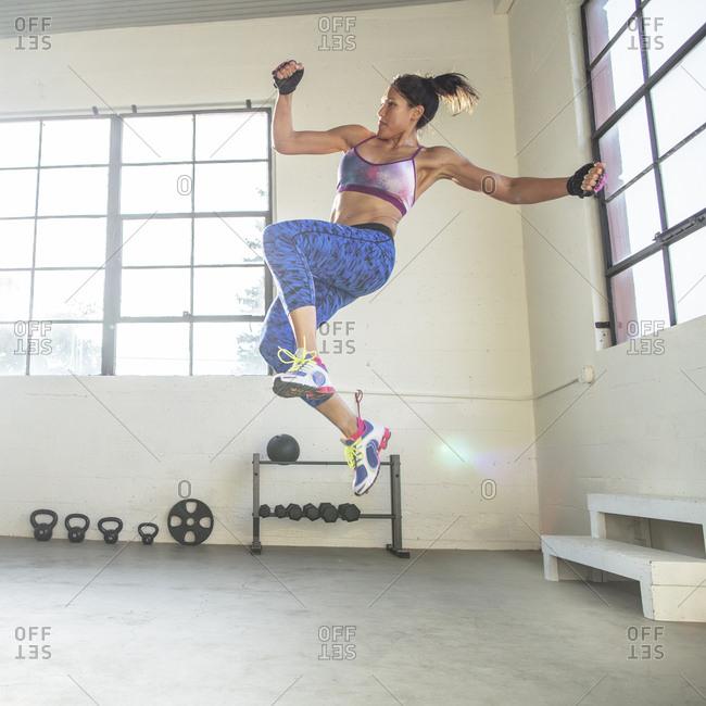 Full length of confident athlete exercising in health club