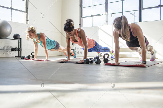 Female athletes doing push-ups on exercise mats in health club