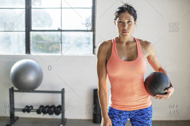 Portrait of female athlete holding medicine ball while standing in gym