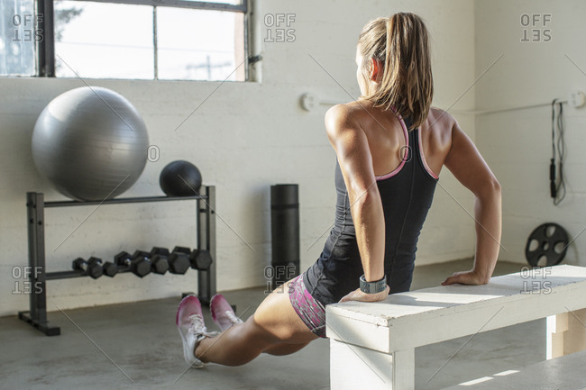 Rear view of female athlete leaning on seat while exercising in gym