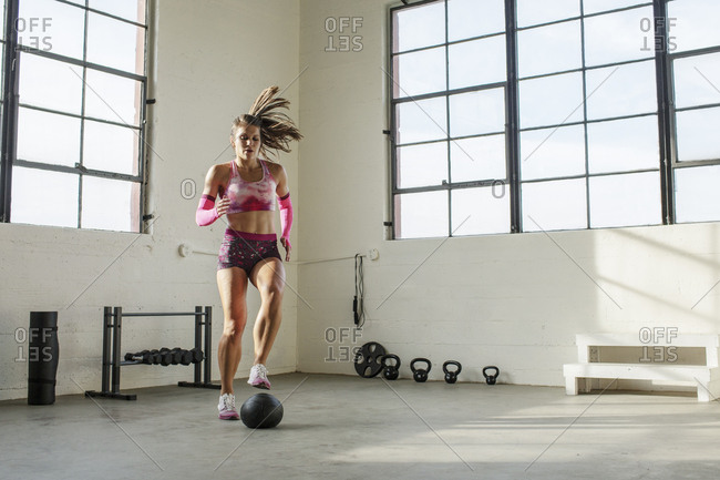 Full length of female athlete exercising with medicine ball in gym