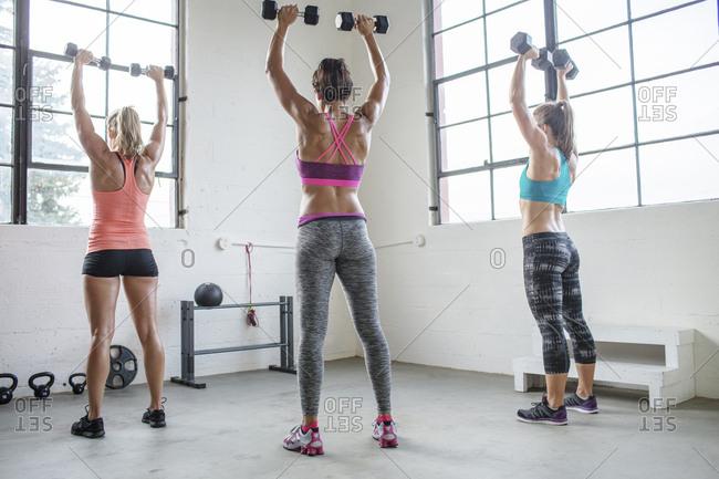 Full length of female athletes lifting dumbbells in health club