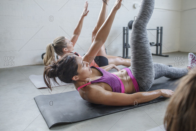 Female athletes stretching body while lying on exercise mats in gym