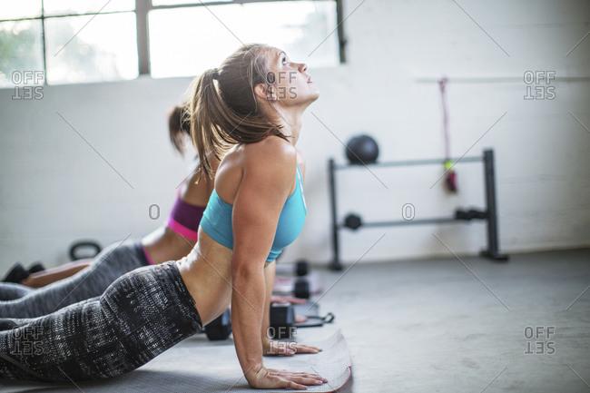 Female athletes practicing upward facing dog position in gym