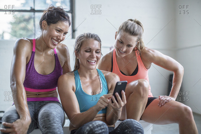 Happy female friends looking at mobile phone being held by woman in gym