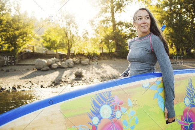 Woman looking away while carrying paddleboard at riverbank