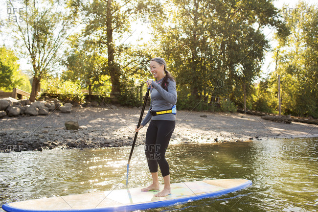 Full length of smiling woman paddle boarding on river