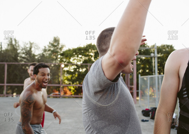 Happy friends shouting while playing basketball at court