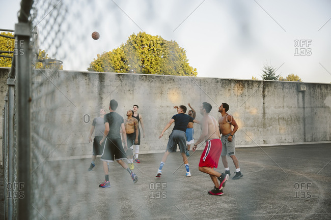 Male friends practicing basketball in court