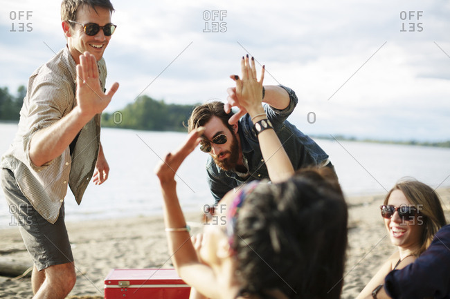 Happy friends doing high-five while enjoying at riverbank against cloudy sky
