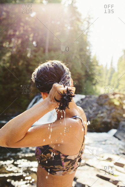 Side view of woman wringing hair while standing in forest at riverbank