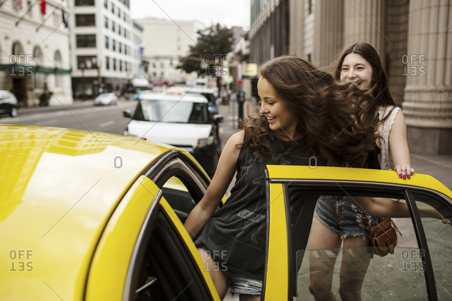 Smiling female friends entering in taxi