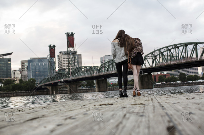 Rear view of female friends standing on pier against Burlington Northern Railroad Bridge 9.6