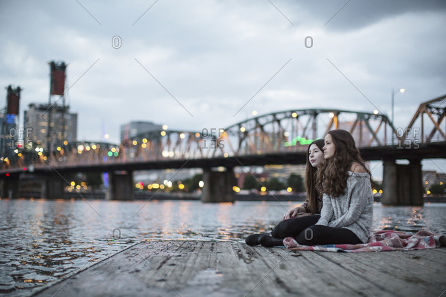 Female friends sitting on pier against Burlington Northern Railroad Bridge 9.6