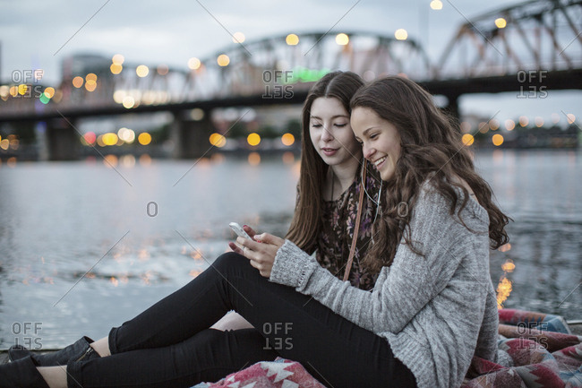 Smiling female friends using smart phone while sitting on pier against Burlington Northern Railroad Bridge 9.6