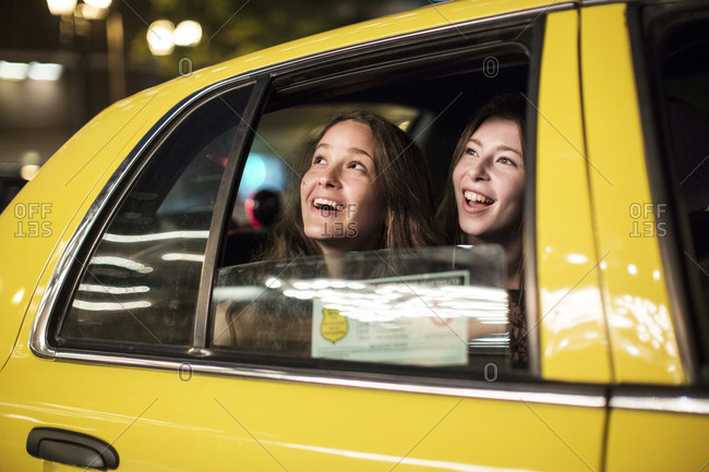 Smiling female friends looking through window while traveling in taxi