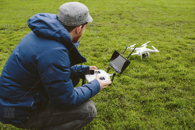 Side view of man flying quadcopter in park