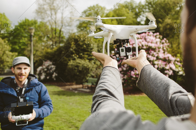 Man operating quadcopter while friend holding it in park