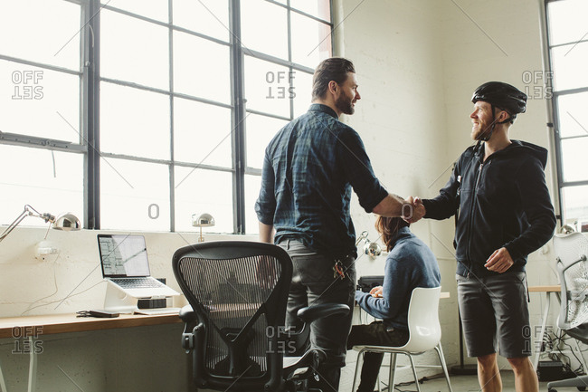 Businessman giving handshake to colleague in creative office