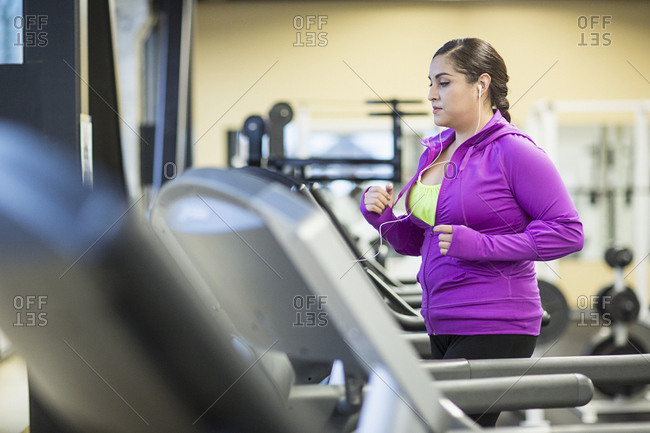 Woman listening music while exercising jogging on treadmill in gym