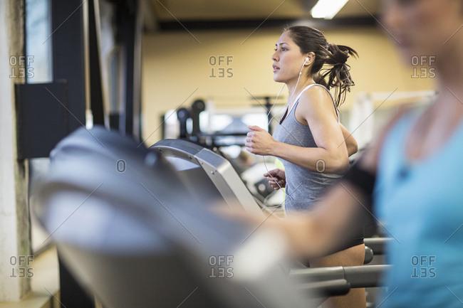Women exercising on treadmills in health club
