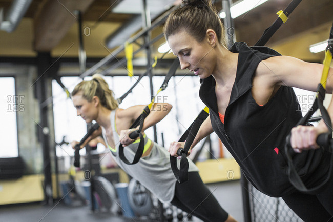 Instructor with woman exercising with resistance bands in gym