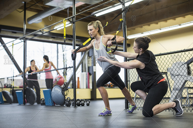 Instructor assisting woman in pulling resistance bands at health club