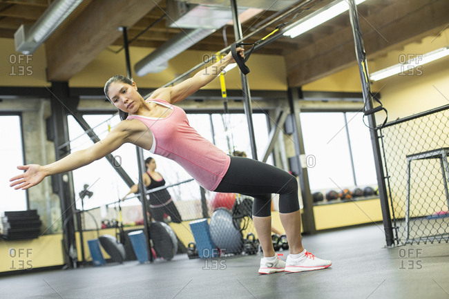 Woman pulling resistance band at gym