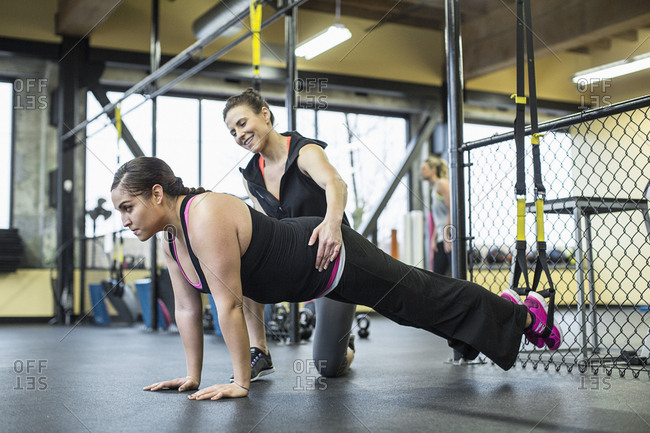 Instructor assisting woman in balancing on resistance band with legs ay gym