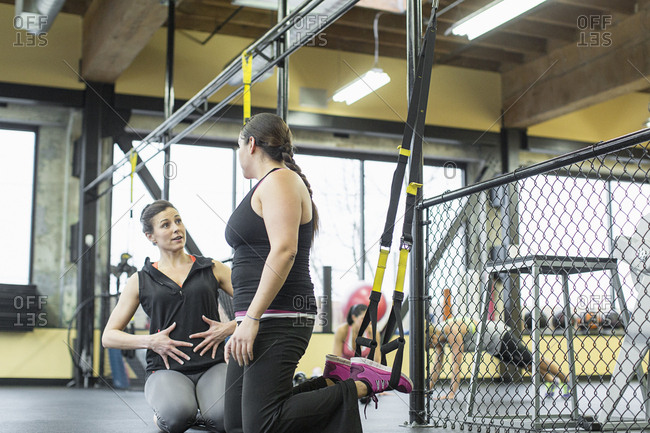 Instructor guiding woman while exercising in gym
