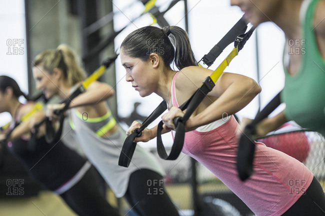 Women pulling resistance bands in gym