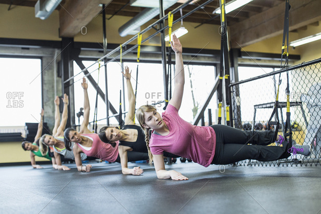 Women practicing side plank pose while balancing on resistance bands in gym
