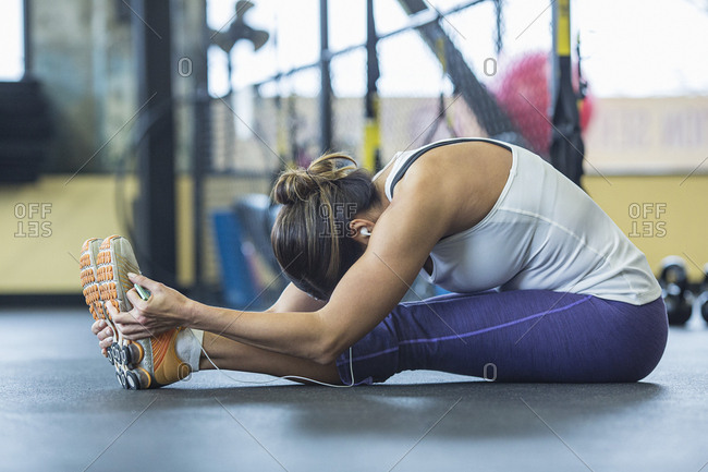 Woman practicing seated forward bend pose in gym