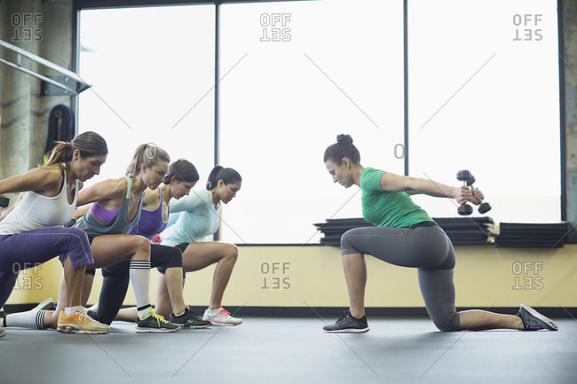 Instructor guiding women in exercising with dumbbells at health club