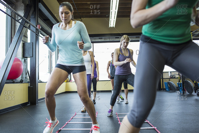 Instructor with women jumping over agility ladder in gym