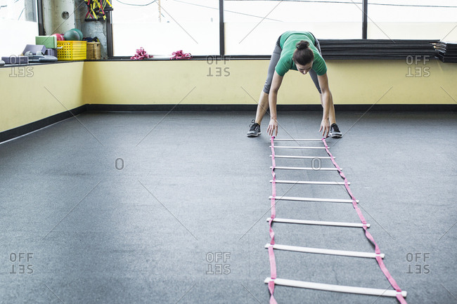 Instructor placing agility ladder on floor in gym