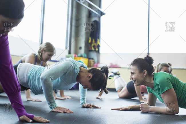 Instructor motivating woman in doing push-ups at gym