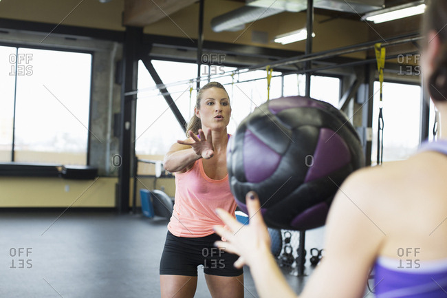 Female friends exercising with medicine ball in health club