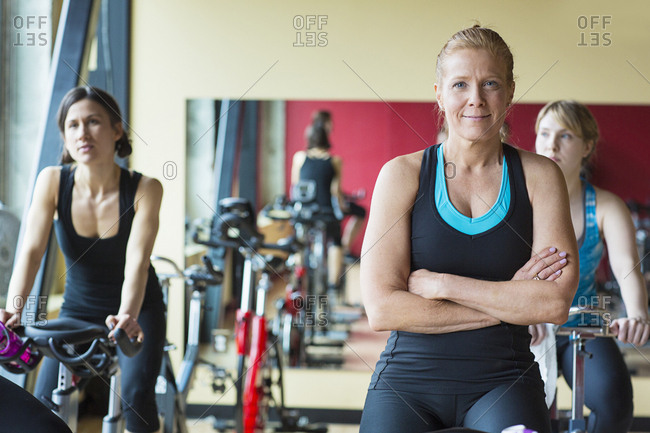 Portrait of woman cycling on exercise bike with friends in gym