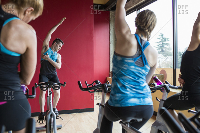 Male instructor exercising with women while sitting on exercise bikes in gym